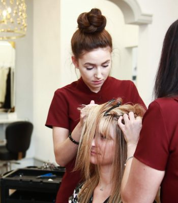 Female member of staff working on clients hair system